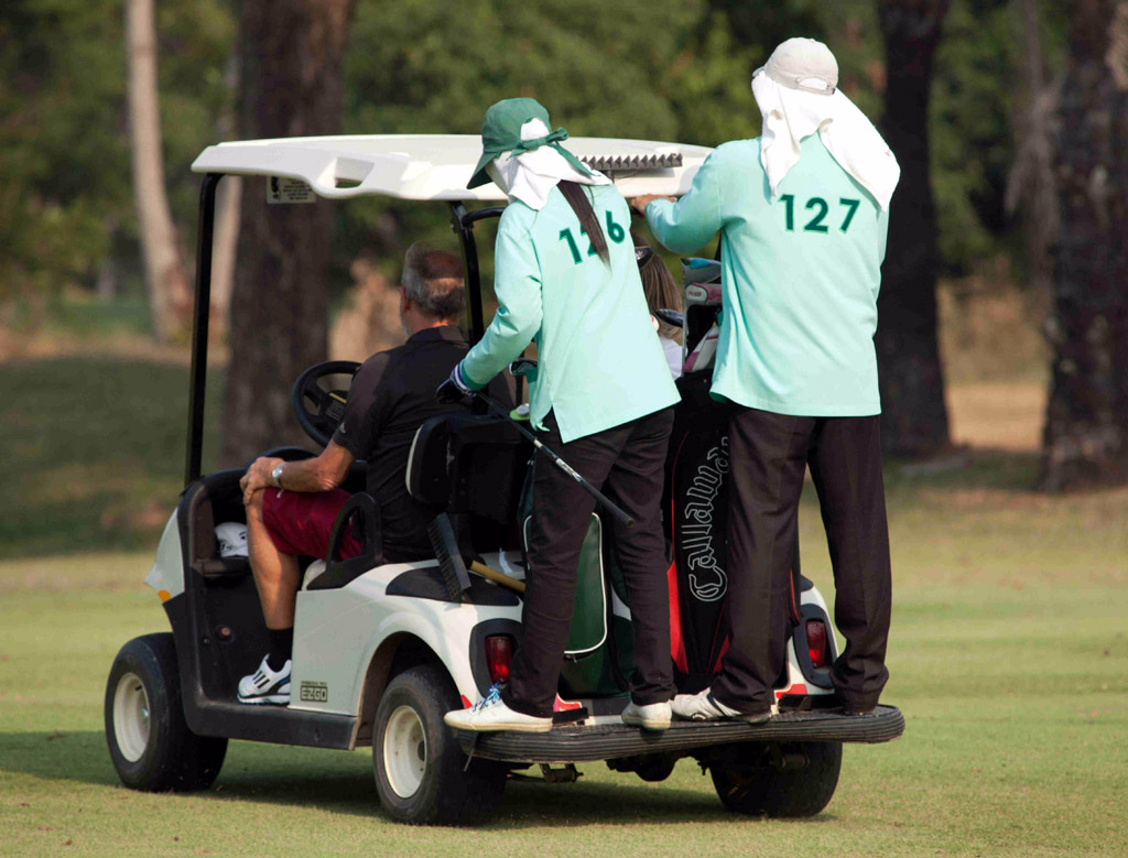 Caddies riding on golf buggy; Majestic Creek golf course, Hua Hin