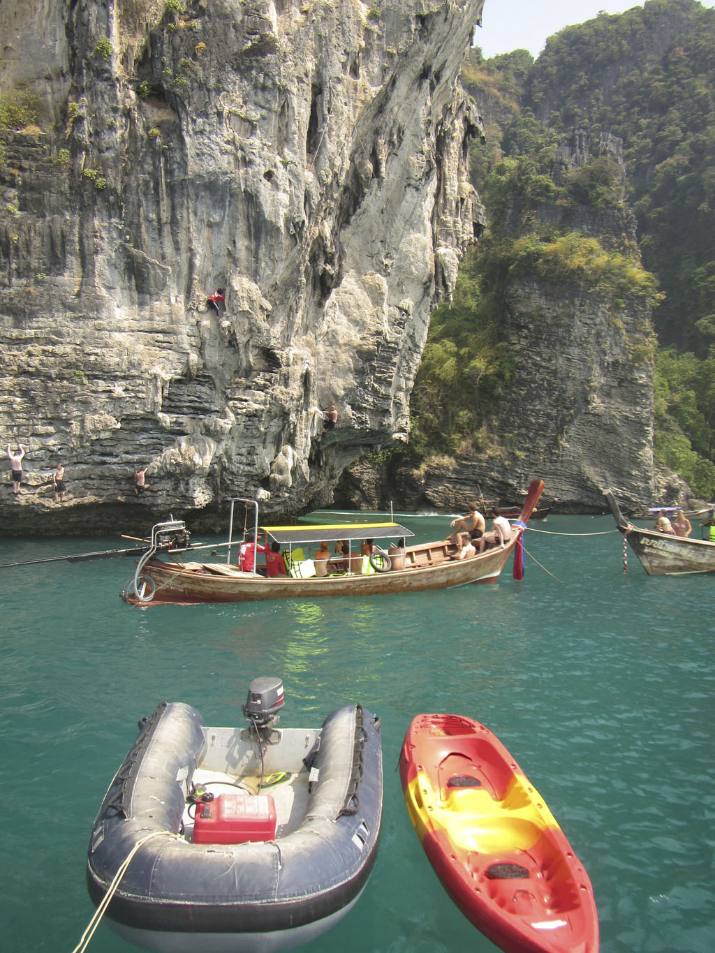 Deep-water solo rockclimbing, inflatable and kayak with nearby longtails