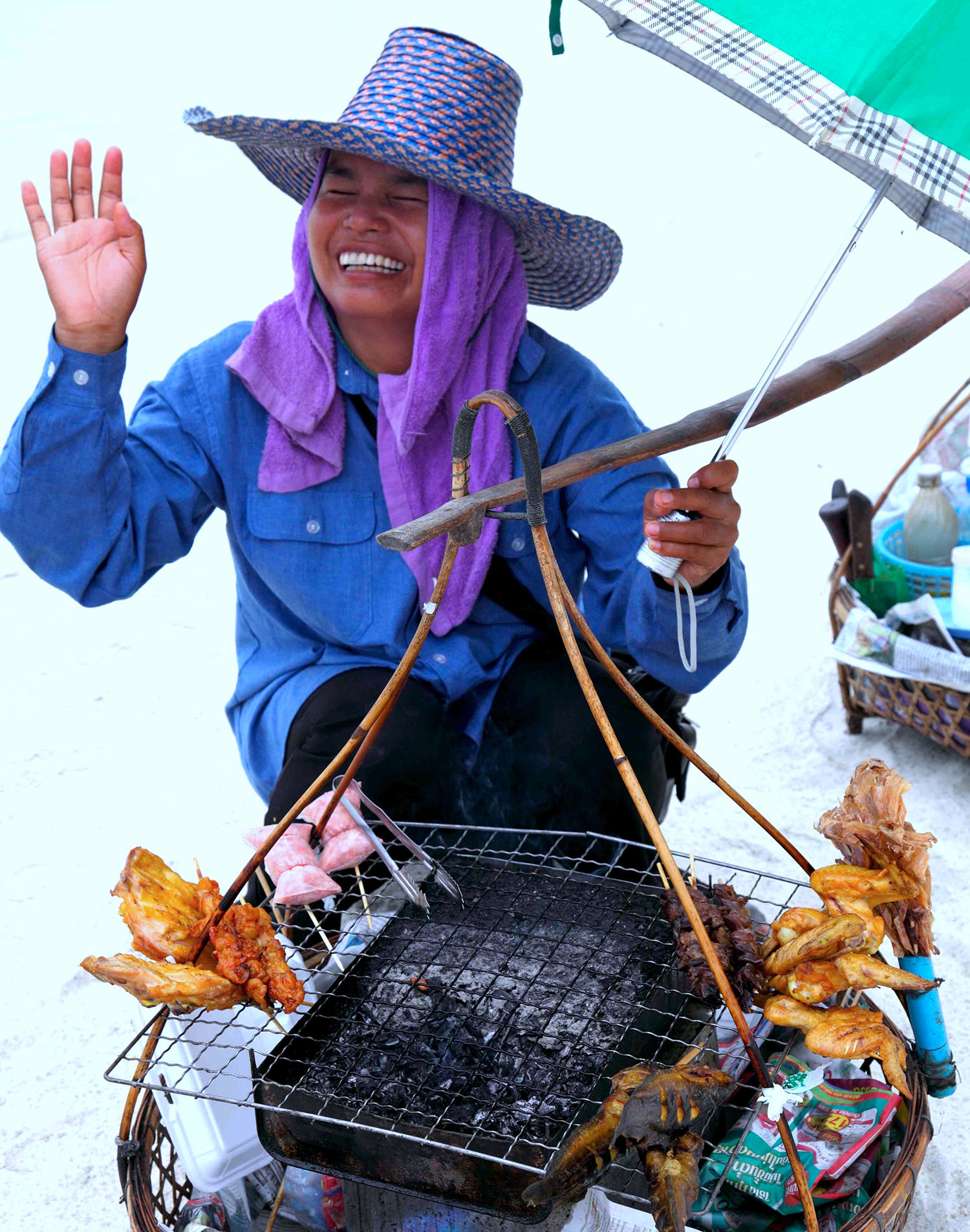 Thai woman, beach vendor, selling fried chicken.