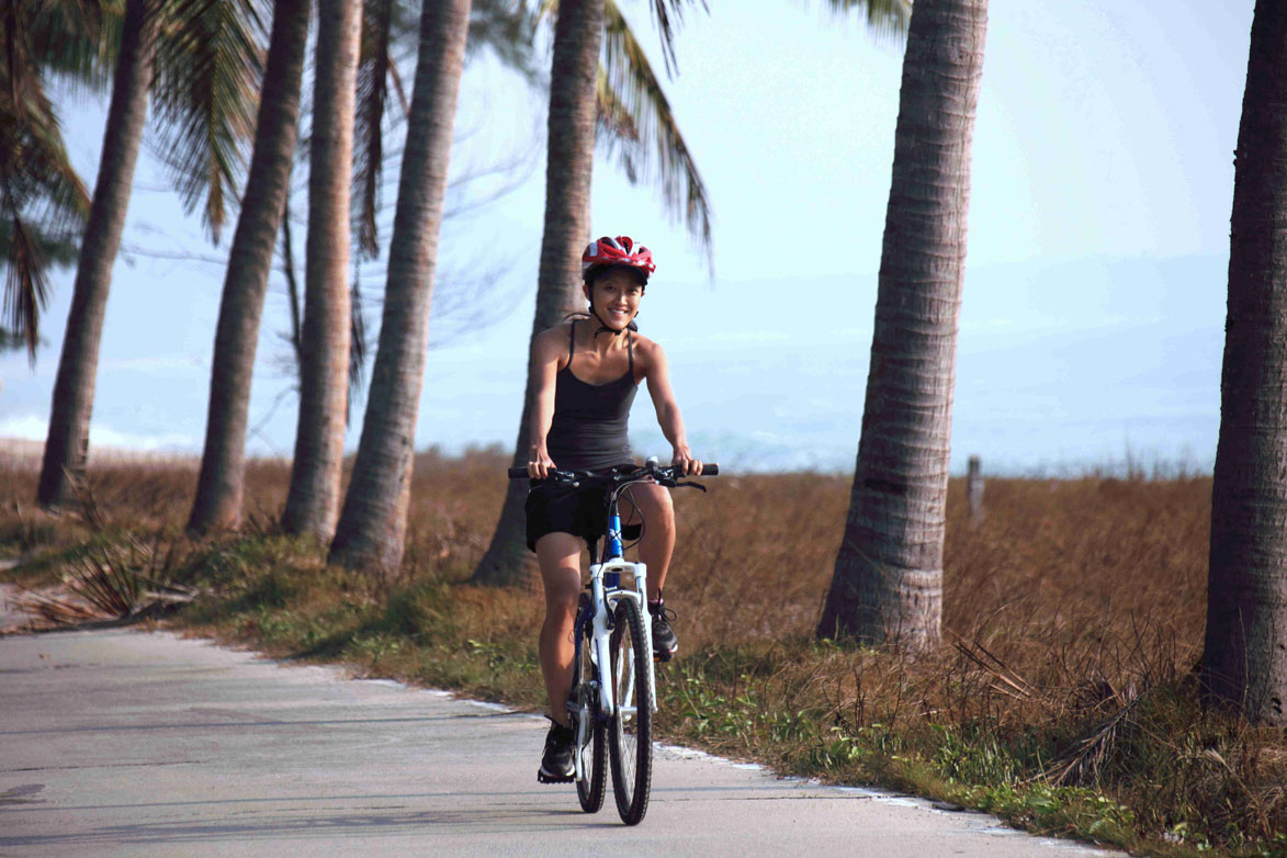 Tourists cycling beside Gulf of Thailand.