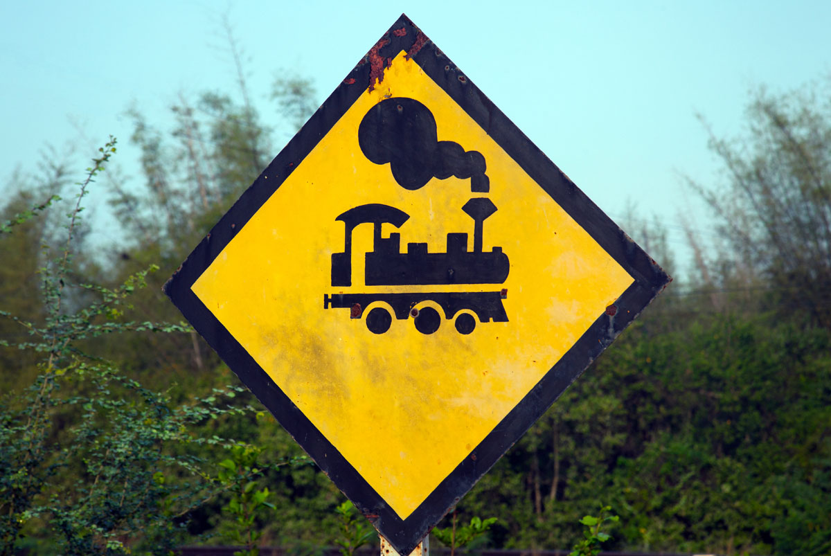 Antique steam train icon and caution sign, at Wang Duan, narrowest part of peninsula Thailand (10.96 km) . Copyright John Borthwick
