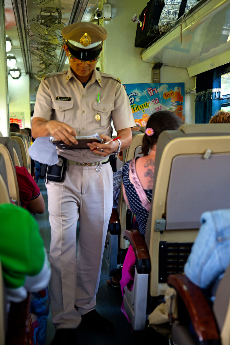 Ticket inspector checking on train, Hua Hin railway station. January 2018. Copyright John Borthwick